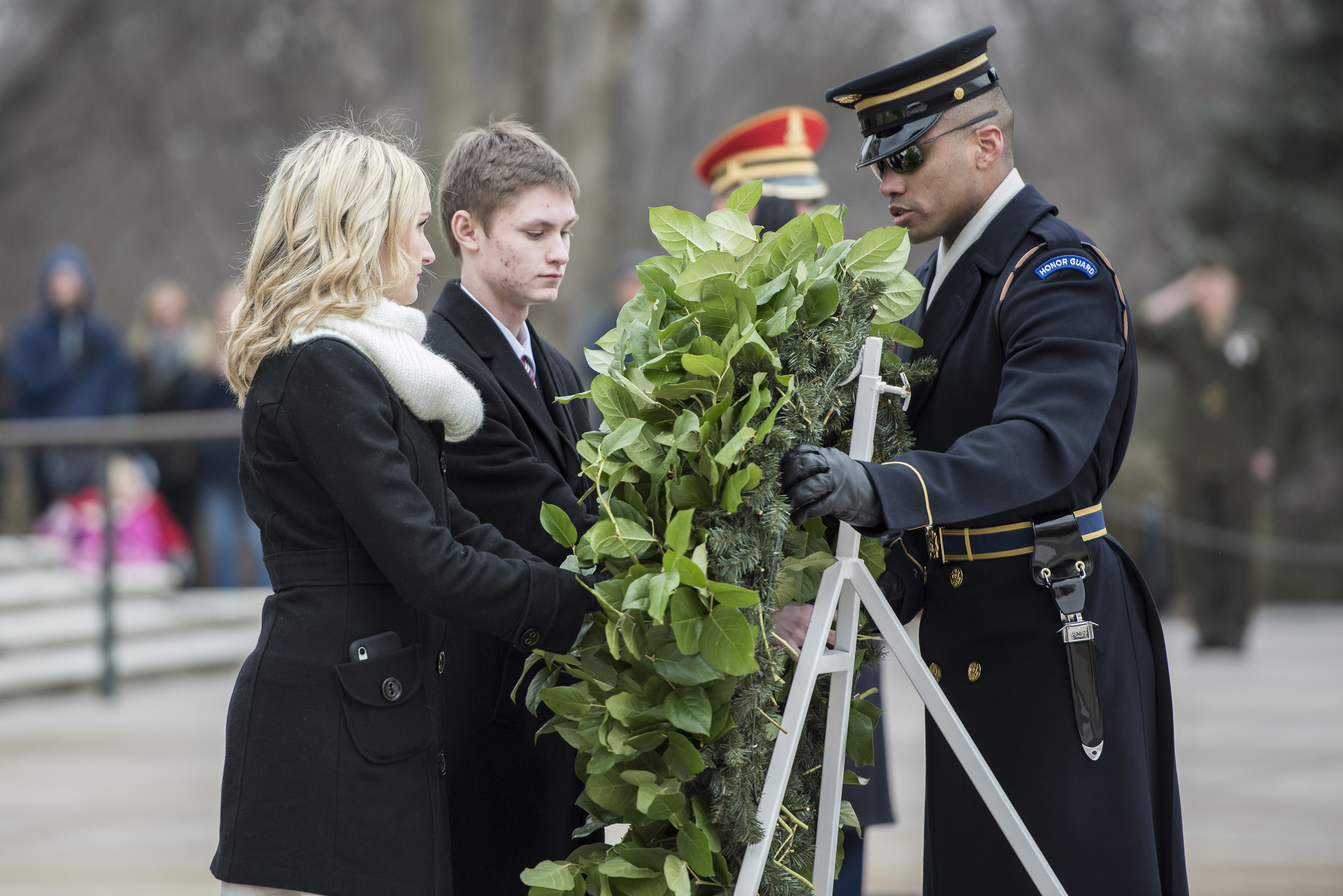 Two teenagers, wearing appropriate attire, participate in a wreath ceremony at the Tomb of the Unknown Soldier