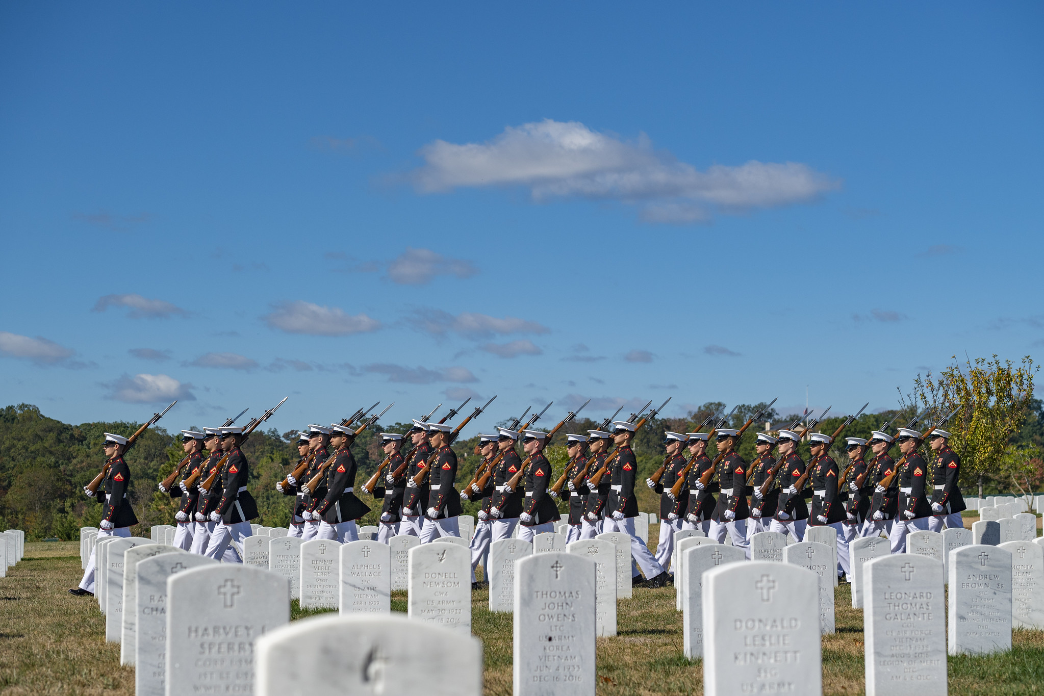 Uniformed Marines march at a military funeral, among gravesites at Arlington National Cemetery