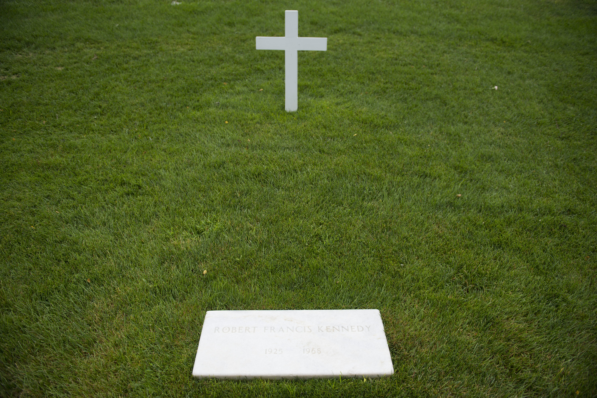 A simple white cross and flat marker at the gravesite of Robert F. Kennedy