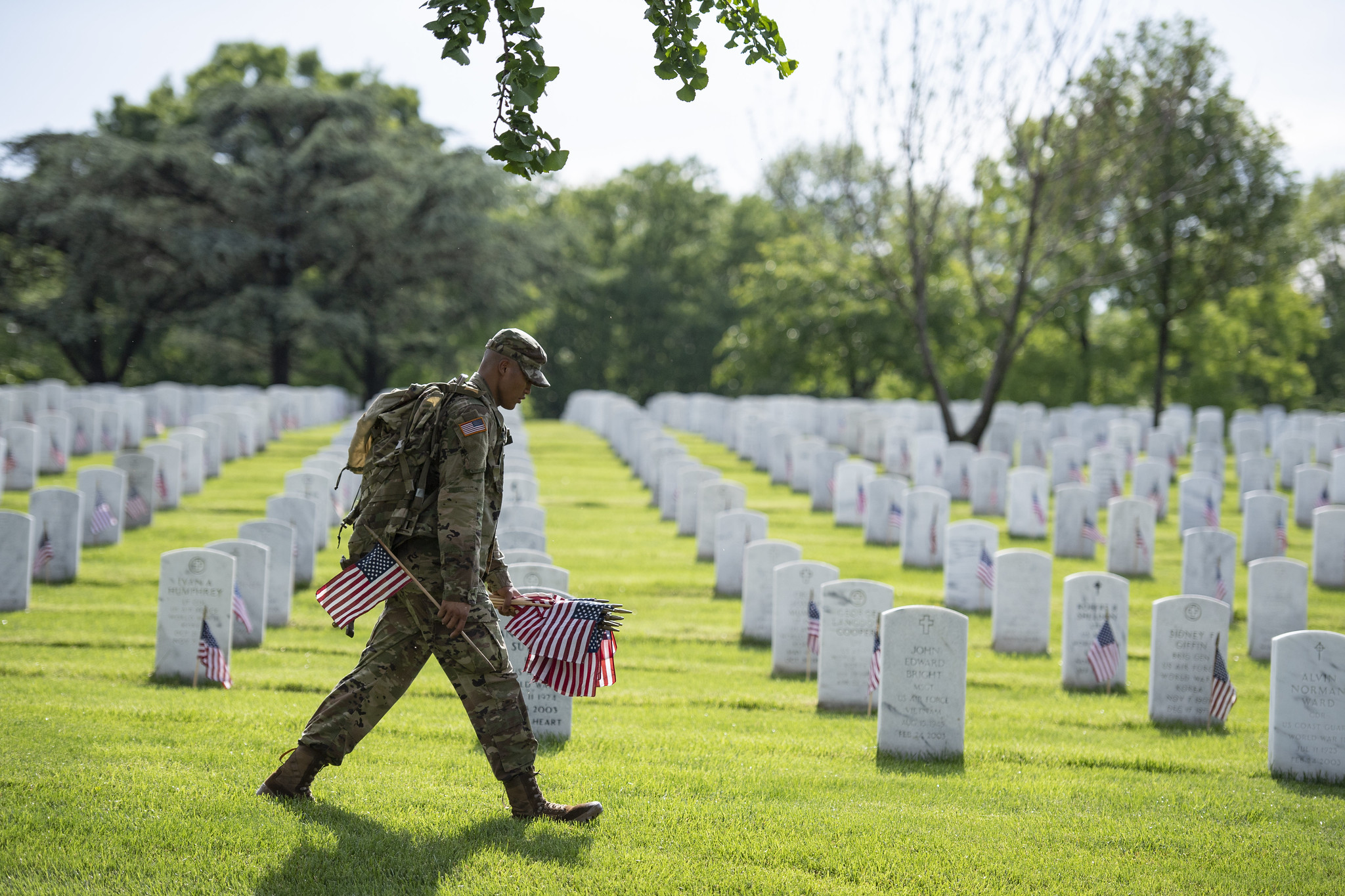 A uniformed soldier places American flags in front of gravestones at Arlington National Cemetery, for Memorial Day